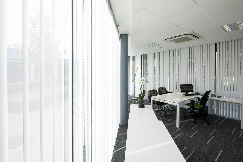 Hochwertiger Sonnenschutz, Sichtschutz und Lichtschutz - Lamellenvorhang - Senkrechtlamellen - Vertikaljalousien - Lamellen Weißer Lamellenvorhang/ Senkrechtlamellen in Fensterlänge im Büro von Dr. Haller + Co. – Selastore®